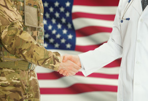 Soldier in uniform and doctor shaking hands with national flag on background - United States